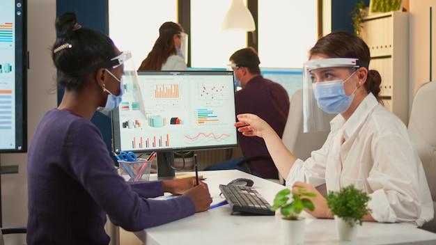 Gerente de escritório explicando para um colega negro estratégia financeira apontando gráficos na área de trabalho usando máscaras e visores. equipe multiétnica trabalhando em empresa com novo normal respeitando a distância social