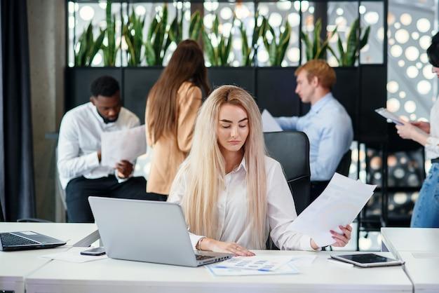Gerente de escritório feminino jovem bastante proposital, inserindo dados do relatório financeiro para laptop no escritório moderno