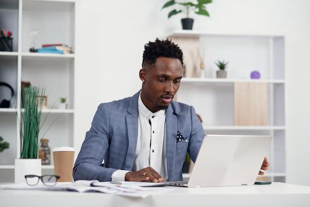 Gerente de escritório jovem de pele escura grave trabalha com diferentes relatórios e laptop de mesa em seu local de trabalho na sala de reuniões no moderno centro de negócios.