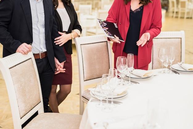 Gerente de evento apresentando salão de banquetes para casal