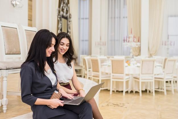 Gerente de eventos mostrando algo no laptop para mulher