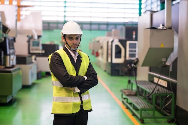 Gerente de fábrica com uniforme formal e capacete de segurança na máquina robô automatizada de torno cnc