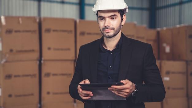 Gerente de fábrica usando computador tablet em armazém ou fábrica. conceito de gestão da cadeia de abastecimento e indústria.