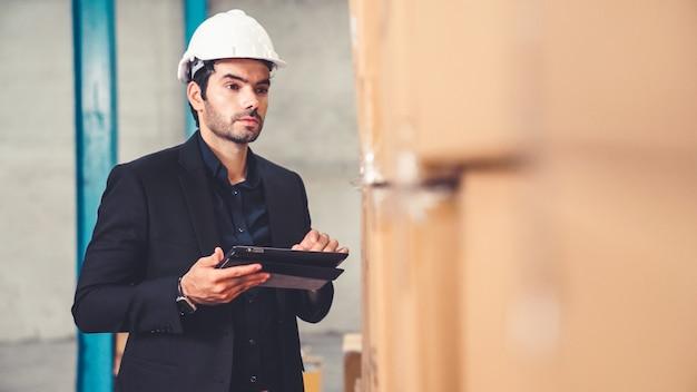 Gerente de fábrica usando computador tablet em armazém