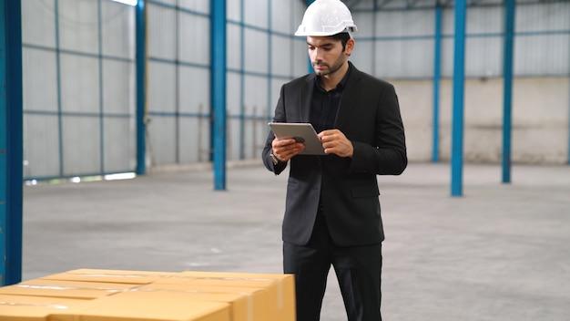 Gerente de fábrica usando computador tablet em depósito ou fábrica