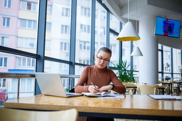 Gerente de garota bem-sucedida em seu próprio escritório com grandes janelas faz um novo plano de negócios de desenvolvimento econômico em um laptop com uma xícara de café. mulher de negócios com documentos sentada a uma mesa de madeira