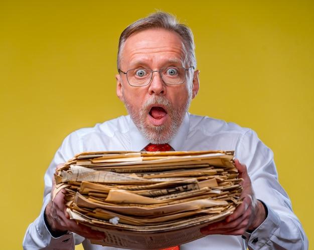 Gerente de gravata vermelha entregando uma grande pilha de documentos