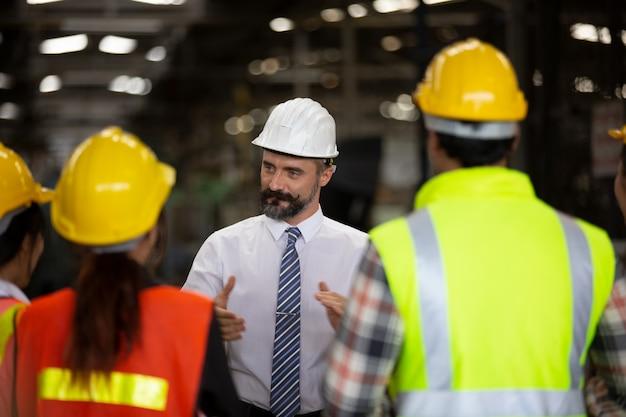 Gerente de grupo de engenheiro e equipe de trabalhadores de fábrica em pé contra a linha de produção.