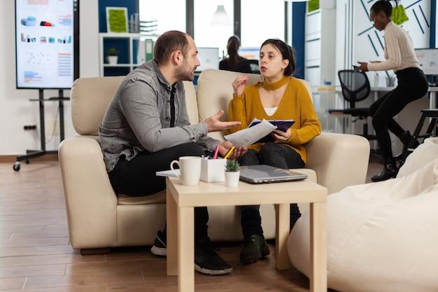 Gerente de homem zangado argumentando com uma funcionária por mau resultado de trabalho, sentado no sofá, enquanto diversos colegas trabalhando com medo no fundo