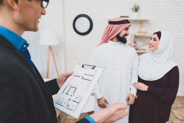 Gerente de imóveis com layout de casa. feliz família árabe amorosa.