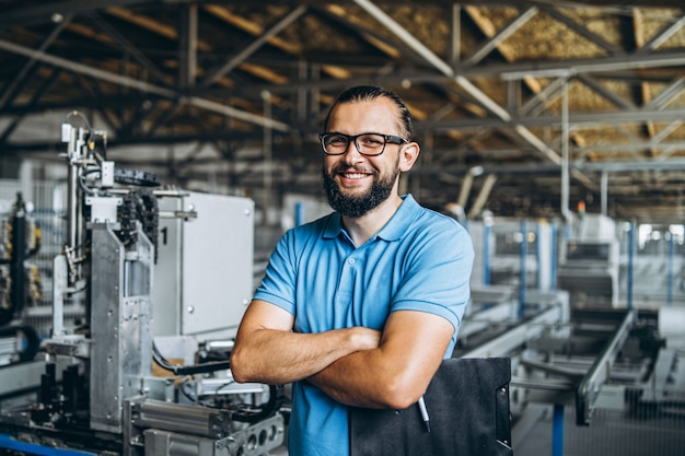 Gerente de jovens engenheiro com barba, verificando manufactory, local de trabalho e máquinas na grande fábrica.