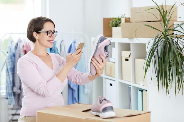 Gerente de loja online de calçados tirando foto da sola do tênis rosa