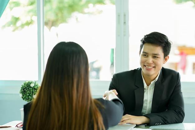Gerente de mão de homem agitar com pessoa graduada após entrevista de emprego