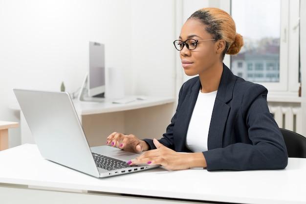 Gerente de mulher de negócios americano africano trabalhando em um laptop.