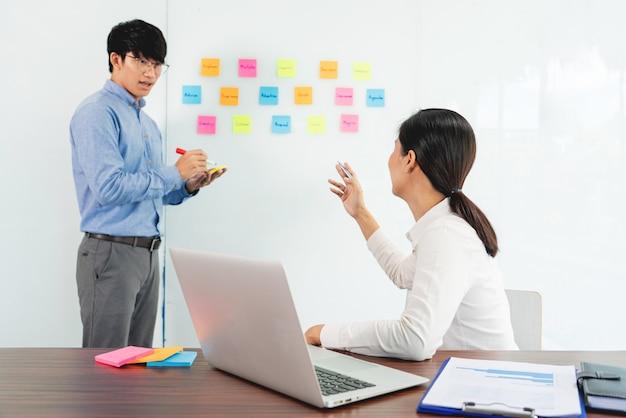 Gerente de negócios, mostrando a ideia para sua equipe e cole muitos memorandos na janela de vidro para o sucesso trabalhando no conceito de escritório, planejamento e gestão criativa de reunião de negócios.