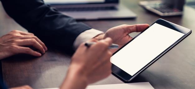 Gerente de negócios segurando a tela em branco do tablet e reunião na mesa no escritório.