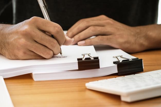 Gerente de negócios verificando e assinando relatórios de documentos