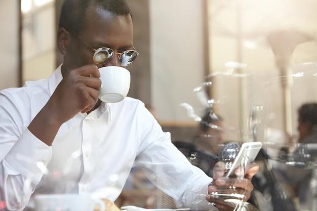 Gerente de preto bonito com roupa formal, verificação de e-mail ou ler notícias do mundo no celular digital, bebendo cappuccino de manhã, sentado à mesa na cafeteria. tecnologia, conexão e comunicação