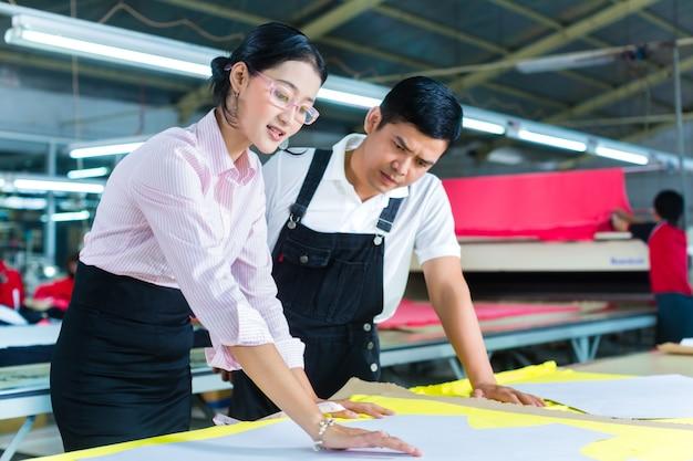 Gerente de produção e designer asiático na fábrica