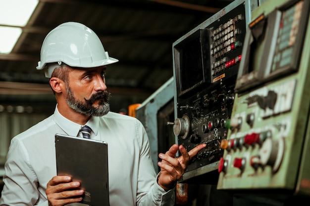 Gerente de projeto sênior trabalhando em fábrica industrial
