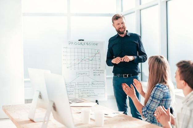 Gerente de projetos explicando aos colaboradores a nova estratégia da empresa.