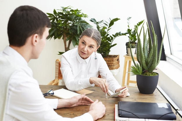 Gerente de recursos humanos da mulher idosa de cabelos escuros confiante na moda, fazendo perguntas durante a entrevista de emprego com o candidato do jovem que está se candidatando à posição de designer. foco seletivo