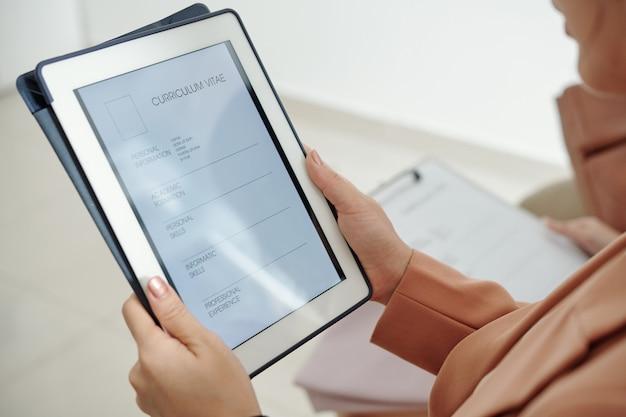 Gerente de recursos humanos segurando um tablet com o curriculum vitae do candidato a emprego