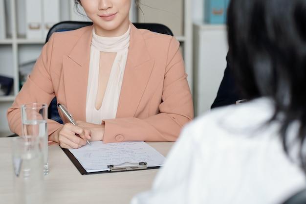 Gerente de recursos humanos sorridente fazendo anotações em um documento ao falar com a candidata em uma entrevista de emprego