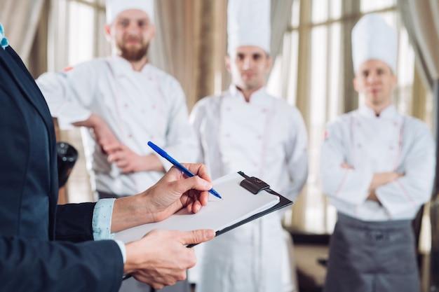 Gerente de restaurante e sua equipe na cozinha. interagindo para chef de cozinha comercial.