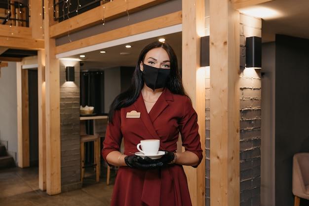 Gerente de restaurante feminino lindo que usa uma máscara preta e luvas descartáveis