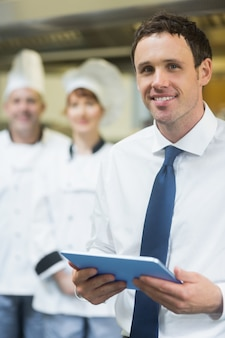 Gerente de restaurante jovem segurando seu tablet