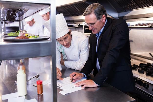 Gerente de restaurante masculino escrevendo na área de transferência enquanto interage com o chefe de cozinha