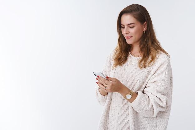 Gerente de smm feminino atraente gerenciando página da web segurando mensagem de digitação de smartphone sorrindo, olhando encantado com a tela do telefone móvel positivo enviando um vídeo amigo engraçado, fundo branco em pé