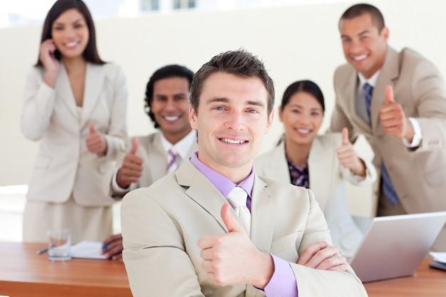 Gerente de sucesso na frente de sua equipe com polegares para cima