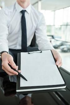 Gerente de vendas contemporâneo em trajes formais apontando para o canto inferior esquerdo do contrato, enquanto oferece ao cliente a assinatura para aprovar o negócio