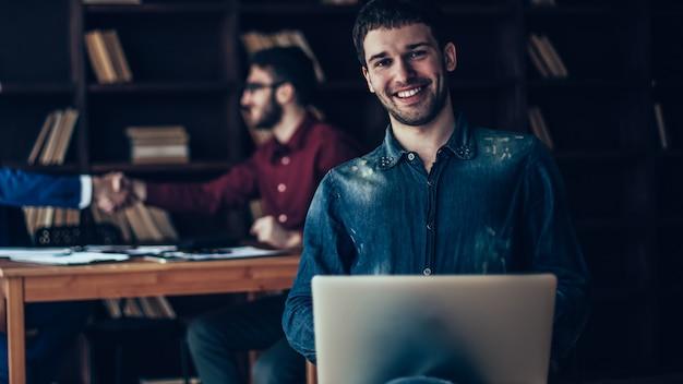 Gerente de vendas criativas com notebook no fundo do aperto de mão de parceiros de negócios em um escritório moderno