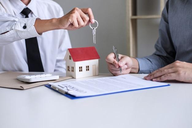 Gerente de vendas dando as chaves para o cliente depois de assinar contrato de locação de aluguel de acordo de compra de venda