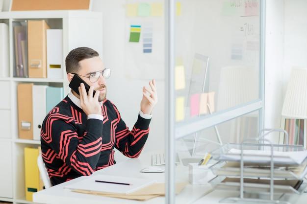 Gerente descontente, gesticulando a mão enquanto fala por telefone