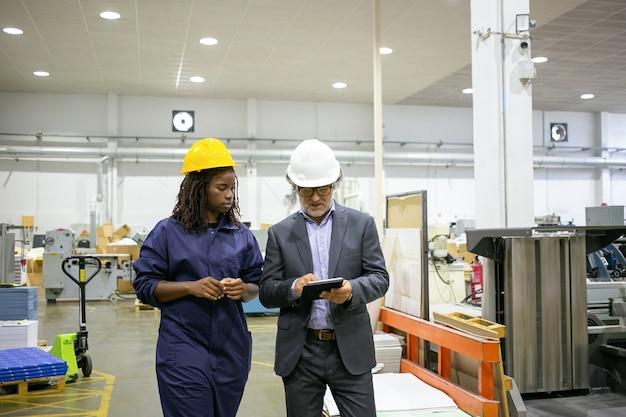 Gerente discutindo o trabalho da fábrica com o trabalhador Foto gratuita