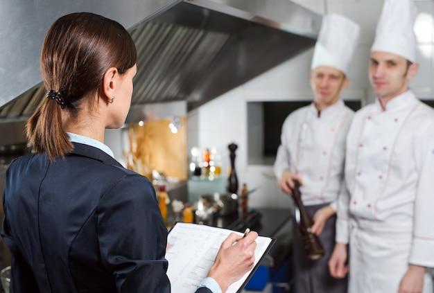 Gerente do restaurante que instrui a sua equipe de funcionários da cozinha comercial