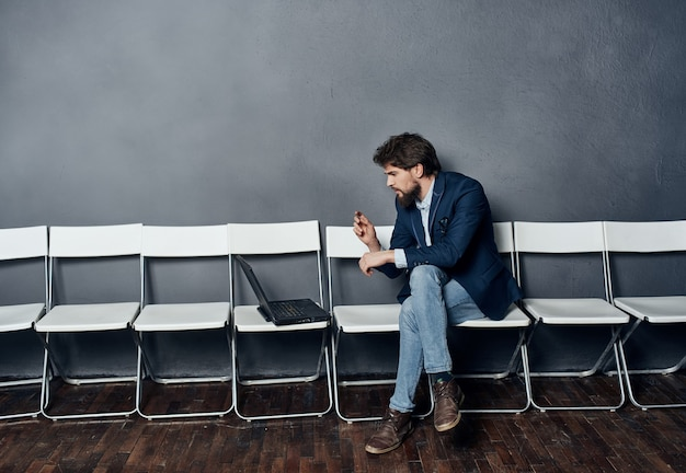 Gerente do sexo masculino com laptop sentado na cadeira à espera da entrevista de emprego profissional
