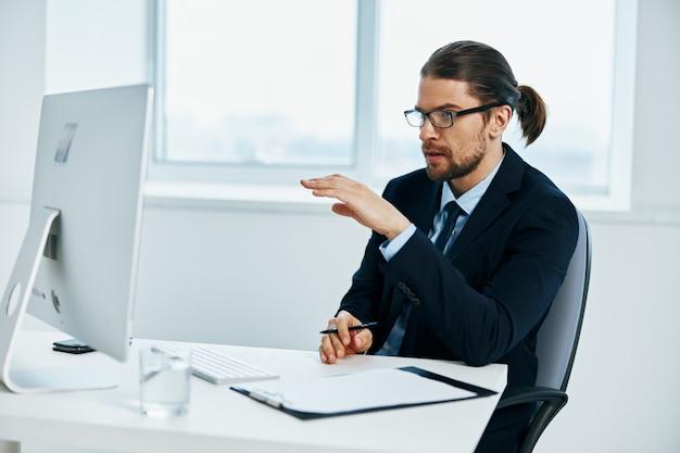 Gerente do sexo masculino trabalhando na frente de um computador documenta o estilo de vida