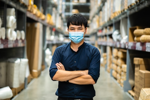 Gerente do sexo masculino usando máscara médica com os braços cruzados na loja durante a pandemia de coronavírus