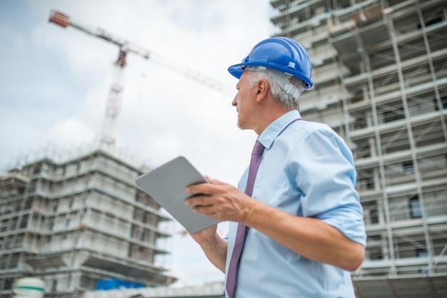 Gerente do site usando seu tablet na frente de um canteiro de obras