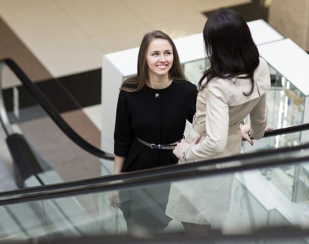 Gerente e cliente em pé na escada do saguão do escritório.