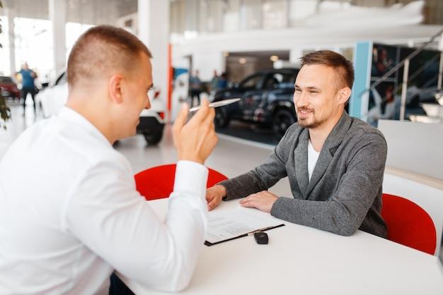 Gerente e comprador fazem a compra do carro novo em showroom.