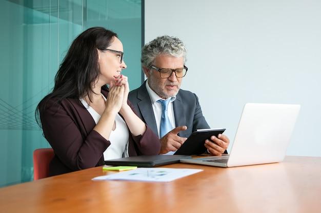 Gerente e executivo discutindo projeto. colegas reunidos à mesa com laptop aberto, usando tablet e conversando.
