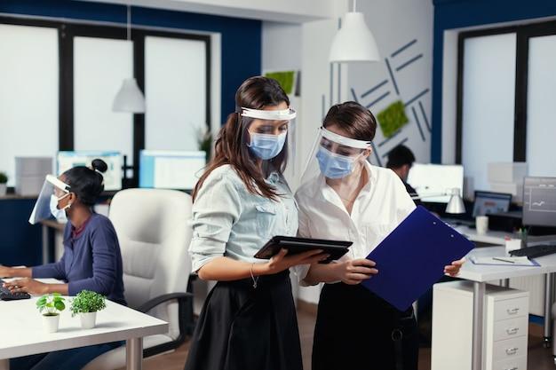 Gerente e funcionário stading discutindo usando tablet pc usando máscara facial. equipe de negócios multiétnica trabalhando respeitando a distância social durante a pandemia global de coronavírus.