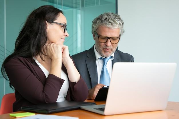 Gerente e investidor discutindo projeto de inicialização. colegas reunidos à mesa com laptop aberto, usando tablet e conversando.
