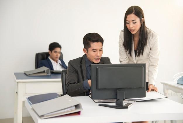 Gerente e secretária consultam para trabalhar na mesa do escritório.